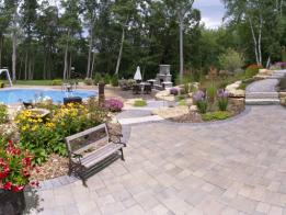 This stunning landscape has it all - a pool, fireplace, paver patio and walkways, outcroppings, and plantings.