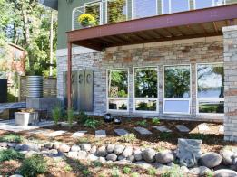 The landscape features a rain barrel system, fire table, and green roof.